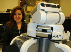 Photo of a student having a close encounter with a PR2 robot at Willow Garage
